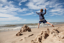 Boy Throwing Rocks Into The Lake, Focus On Pile Of Sand