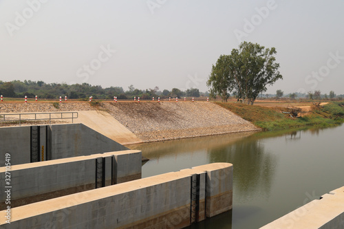 Closeup of a part of concrete dam with natural background. Wallpaper Mural