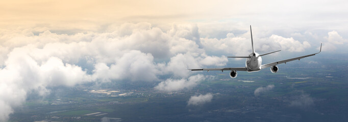 passenger airplane is flying iover the clouds