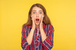 canvas print picture - Oh my god, wow! Portrait of shocked amazed ginger girl in checkered shirt looking at camera with open mouth and surprised big eyes, astonishment. indoor studio shot isolated on yellow background