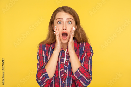 Valokuva Oh my god, wow! Portrait of shocked amazed ginger girl in checkered shirt looking at camera with open mouth and surprised big eyes, astonishment