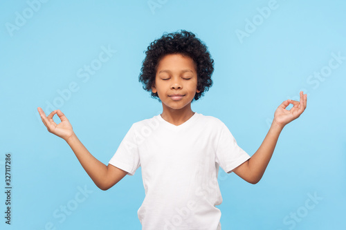 Photo Portrait of peaceful cute little boy holding fingers in mudra gesture and meditating with closed eyes, feeling calm positive and relaxed, yoga practice