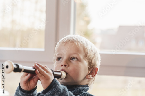 infant boy playing flute Wallpaper Mural