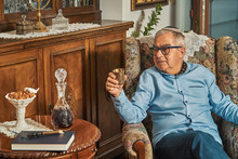 Senior Jew In Armchair Drinks Wine In Traditional Home