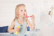 Portrait Of Funny Little Girl Blowing Bubbles At Home