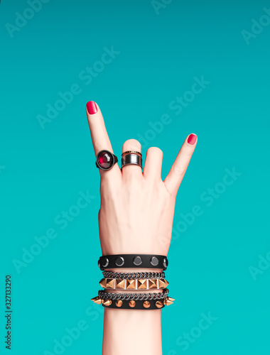 Rock hand sign, female hand punk rock gesture with gold wrist bracelets and finger rings isolated, creative art protest banner, fashion hipster accessories, 3d rendering Wall mural