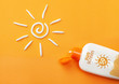 Sunscreen on orange background. Plastic bottle of sun protection and white sun-shaped cream
