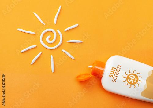 Fototapeta Sunscreen on orange background. Plastic bottle of sun protection and white sun-shaped cream obraz