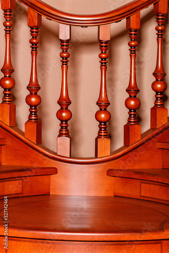 Photo Element of a wooden staircase with carved balusters and mahogany railings