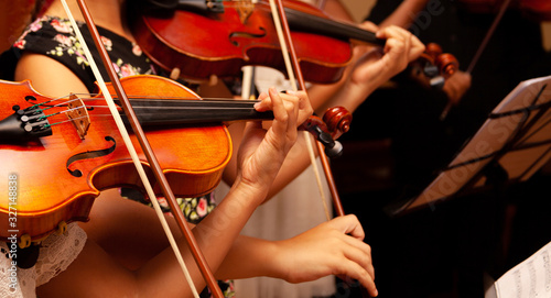 Photo Row, group of anonymous violin players, children, people playing, bows in hands, stands in front, closeup