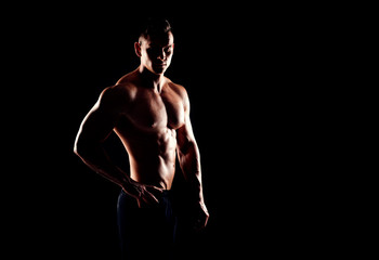 Strong, fit and sporty bodybuilder man over black background.
