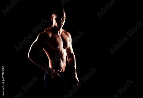 obraz PCV Strong, fit and sporty bodybuilder man over black background.