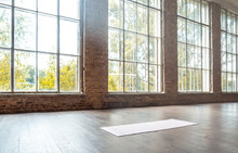 White Mat On Wooden Floor Empty Modern Spacious Gym Private Fitness Classroom Sport Club Studio Class Training Daylight Big Windows With Brick Walls Workout Yoga Healthy Lifestyle Concept Copy Space.