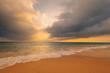 Waves on sandy ocean beach under a beautiful sunset sky with clouds on Sri Lanka island.