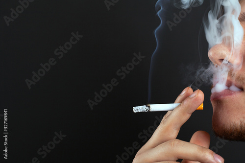 Fototapety, obrazy: young unshaven guy smokes a cigarette in white smoke on a dark background copy space