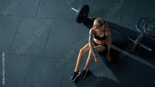 Photo Barbell girl Crossfit woman sitting on floor at gym looking into the distance, resting after cross-fit workout with barbell View from above Concept of power, healthy lifestyle, sport Copy free space