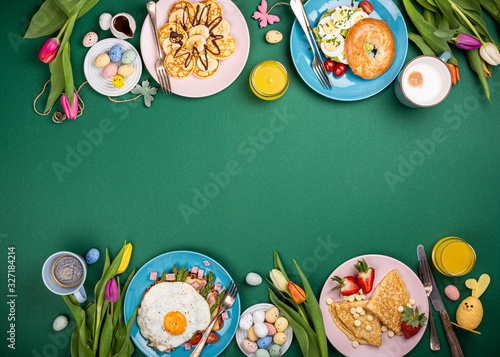 Fototapeta Easter breakfast flat lay with scrambled eggs bagels, tulips, pancakes, bread toast with fried egg and green asparagus, colored quail eggs and spring holidays decorations. Top view. Copy space. obraz
