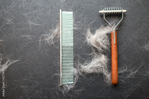Vászonkép Comb and brush with wool on the table, Pet grooming concept.