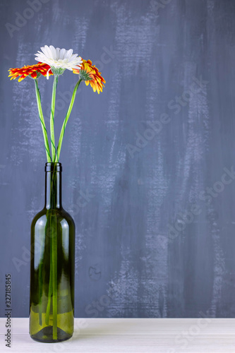 Photo Bouquet of gerberas in green bottle on an isolated dark background