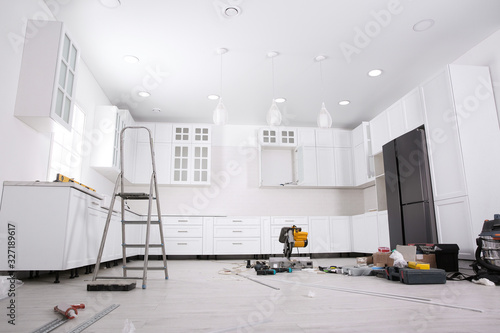 Fotografía Renovated kitchen interior with stylish furniture, refrigerator and maintenance
