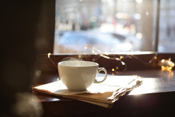 Delicious morning coffee and newspaper near window, indoors