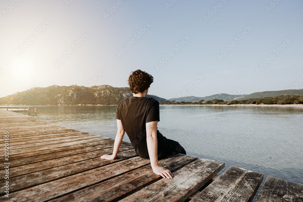 Fototapeta Mensch sitz im Sommer auf einem Steg am See und genießt den wunderschönen Ausblick auf das Wasser und die Berge bei Sonnenuntergang