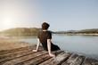 Mensch sitz im Sommer auf einem Steg am See und genießt den wunderschönen Ausblick auf das Wasser und die Berge bei Sonnenuntergang