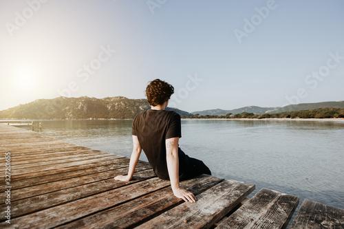 Obraz Mensch sitz im Sommer auf einem Steg am See und genießt den wunderschönen Ausblick auf das Wasser und die Berge bei Sonnenuntergang - fototapety do salonu