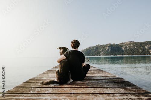Mensch umarmt Hund auf einem Steg mit Blick auf einen wunderschönen See mit Berg Canvas Print