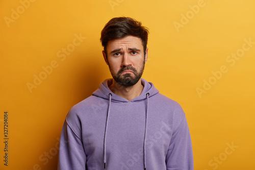 Valokuvatapetti Unamused sad miserable guy purses lips, frowns face with dissatisfaction, wears