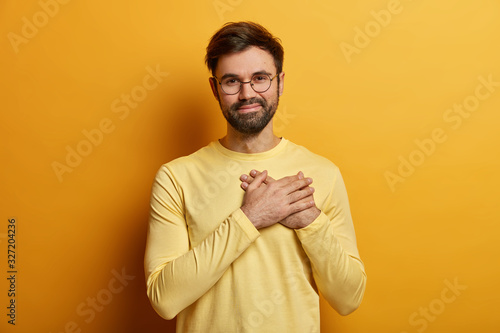 Photo Handsome bearded guy keeps hands on heart, expresses sincere emotions, appreciates help and heartwarming words, stands thankful, wears casual yellow jumper, poses indoor