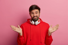Indecisive Millennial Man With Beard, Shrugs Shoulders, Raises Palms, Dressed In Red Sweatshirt, Uses Stereo Headphones, Smirks Problematic, Cant Understand Anything, Poses Over Rosy Pastel Wall
