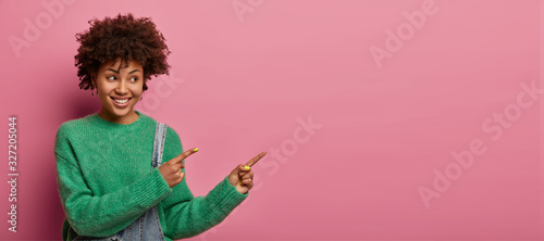 Positive ethnic woman points at product, suggests check it out, indicates right with happy smile, rejoices nice advertisement, wears green sweater, poses against pink background. Promo concept