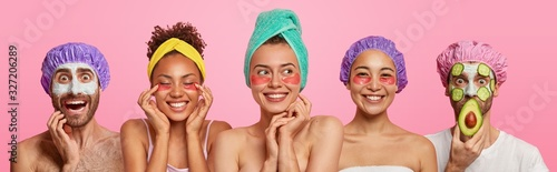 Fototapeta Three mixed race women apply gel patches under eyes to reduce wrinkles, express positive emotions, two men wear clay masks with cucumber slices, bath caps. Set of five people get beauty treatments obraz
