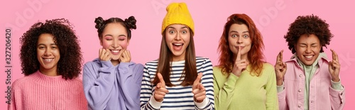 Multiracial women express positive emotions, make different gestures stand in row over rosy wall. Ginger woman shows hush sign, Afro female crosses finger for good luck, millennial girl points at you