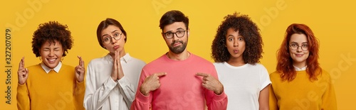 Unimpressed bearded man points at himself, four women stand near him, pray and beg for something, have glad expressions, wear spectacles, isolated over yellow background Tableau sur Toile