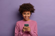 canvas print picture - Portrait of lovely ethnic woman holds modern mobile phone, uses electronic device on surfing web, looks positively at camera, connected to wireless internet, wears casual sweater, poses indoor