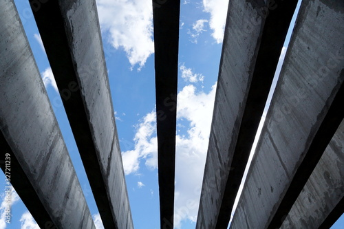 Up view to the blue sky with white clouds through parallel architectural concret Canvas Print
