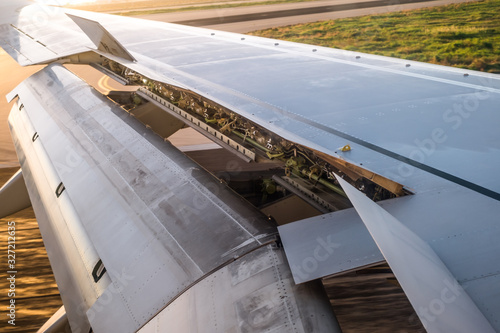 airplane window view of wing and flaps after landing at the airport Canvas Print