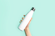 Close-up Of Female Hand, Holding White Reusable Steel Stainless Eco Thermo Water Bottle, Isolated On Background Of Cyan, Aqua Menthe Color. Be Plastic Free. Zero Waste.