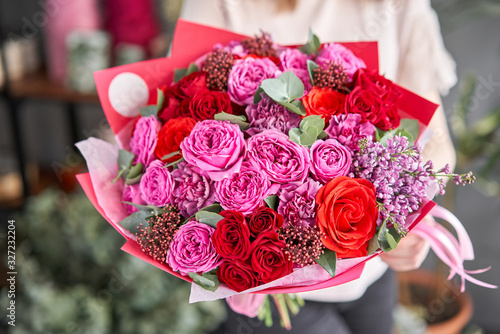 Bright berry color, Beautiful bouquet of mixed flowers in womans hands. the work of the florist at a flower shop. Delivery fresh cut flower. European floral shop. © malkovkosta