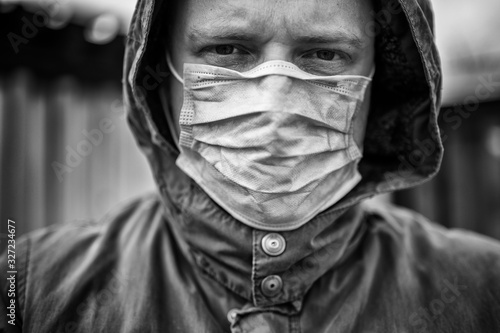 Foto Aufnahme eines ernst blickenden Mannes mit Mundschutz zum Thema Infektionskrankh