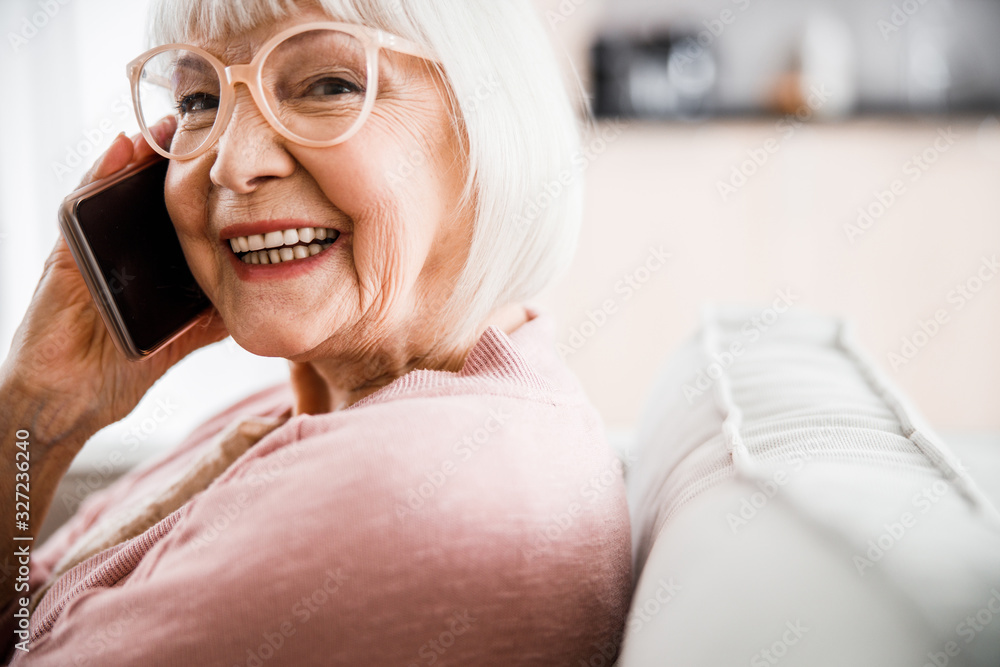 Fototapeta Cheerful old lady in glasses talking on cellphone