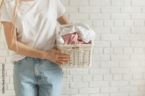 Canvastavla Woman holding wicker basket with heap of different clothes, on bricks wall backg
