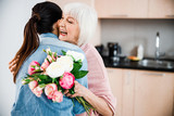 Fototapeta Kwiaty - Cheerful old lady holding flowers and hugging granddaughter