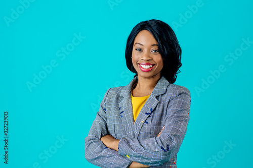 Portrait of a happy smiling young woman in business jacket with arms crossed isolated on blue