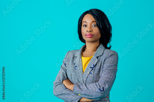 Fototapety, obrazy: Portrait of a young woman in business jacket with arms crossed isolated on blue