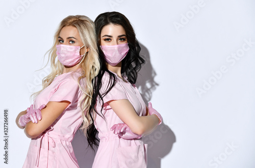 Two ladies in pink scrubs, disposable gloves and medical masks posing isolated on white. Medical staff, cosmetologist. Close up