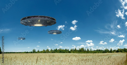 Cuadros en Lienzo UFO, an alien plate hovering over the field, hovering motionless in the air