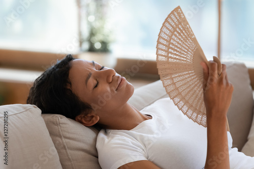 Obraz na plátne Exhausted biracial woman wave with hand fan suffering from heatstroke